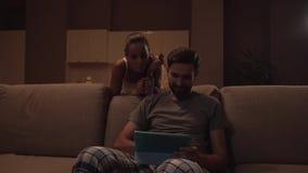 Mädchen nimmt ein Plätzchen und geht weg von Küche Sie hält Schale Frau stoppes hinter Sofa, in dem Kerl sitzt und hält stock footage