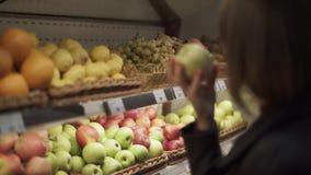 Mädchen nimmt einen Apfel von einem Regal in einem Supermarkt stock video footage