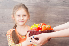 Mädchen nimmt Handkorb mit Gemüse Stockbild
