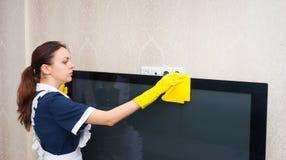 Mädchen oder Haushälterin, die einen Fernseher säubern Lizenzfreie Stockbilder