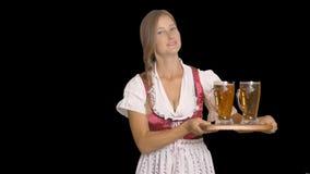 Mädchen Oktoberfest A in einem nationalen Kostüm von Bayern hält die Bäckerei mit zwei Bieren auf einem hölzernen Behälter und Lä stock footage