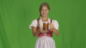 Mädchen Oktoberfest A in einem nationalen Kostüm von Bayern hält ein Glas Bier und lächelt, es, einen grünen Schirm demonstrieren stock footage