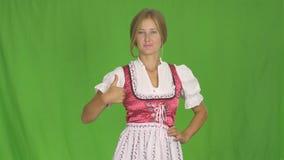 Mädchen Oktoberfest A im bayerischen nationalen Kostüm lächelt und zeigt Klasse Grüner Bildschirm stock video footage