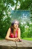 Mädchen online im Park Lizenzfreies Stockbild