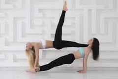 Mädchen ` Paare mit Yoga acro Praxis des blonden und dunklen Haares, weißes abstraktes backgound Lizenzfreies Stockbild