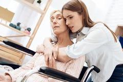 Mädchen pflegt ältere Frau zu Hause Mädchen umarmt die Frau, gesorgt um sie stockbilder