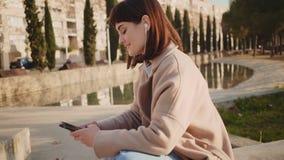 Mädchen plaudert mit jemand telefonisch im Park stock video