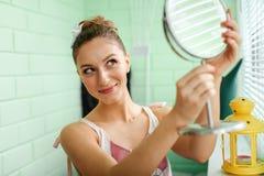 Mädchen putzt sich vor Spiegel Stockbild