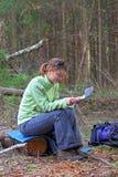 Mädchen-Reisender im Holz eine Karte lesend Stockfotos