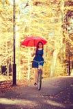 Mädchen reitet das Fahrrad mit Regenschirm Stockfotografie