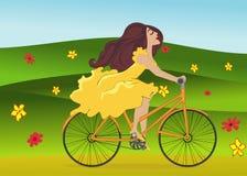 Mädchen reitet Fahrrad auf blühendes Frühlingsfeld Lizenzfreies Stockbild