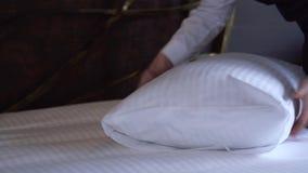 Mädchen richtet ein Kissen in einem kleinen, gemütlichen Hotelzimmer gerade stock video