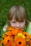 Mädchen, riechend Blumen Stockfotos