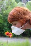 Mädchen in riechender Blume des Respirators Lizenzfreies Stockfoto