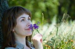 Mädchen riecht Blumen Lizenzfreie Stockfotografie