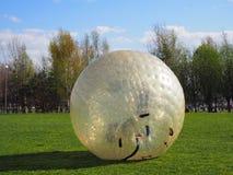 Mädchen rollen unten in einem riesigen Blasenballon stockbilder