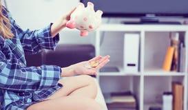 Mädchen ` s übergibt das Halten von einem Sparschwein und das Gießen von bitcoins aus ihm heraus Konzept des Falles in den Wert v stockfotos
