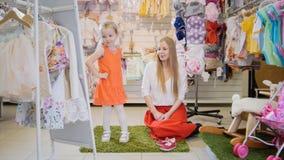 Mädchen ` s Einkaufen - blondes kleines Mädchen mit Mama wählt Modekleid im Speicher von Kinderkleidung Lizenzfreies Stockfoto