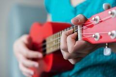Mädchen ` s Finger, die Akkord auf fretboard der roten Ukulele spielen lizenzfreie stockbilder