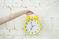 Mädchen ` s Hand, die gelben Wecker auf weißem Ziegelstein backgroung hält Stockfoto