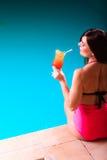 Mädchen s im Badeanzug am Poolside mit Cocktailglas sideview Stockfotos