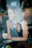 Mädchen saß im Fenster einer Kaffeestube Stockfoto