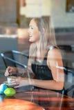 Mädchen saß im Fenster eines trinkenden Kaffees der Kaffeestube Stockfotos