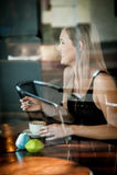 Mädchen saß im Fenster eines trinkenden Kaffees der Kaffeestube Stockfotografie