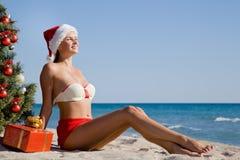 Mädchen in Sankt-Hut Sonne und Wärme auf dem Strandurlaubsort während der Weihnachtsfeiertage genießend Lizenzfreie Stockfotografie