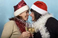 Mädchen in Santa Claus-Hüten und -champagner Lizenzfreie Stockfotos