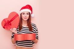 Mädchen in Santa Claus-Hut mit Geschenkbox Stockfotografie