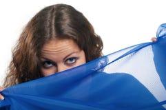 Mädchen schaut über blauem Schleier Lizenzfreies Stockbild