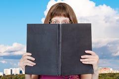 Mädchen schaut über großem Buch und weißer Wolke Stockfoto