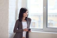 Mädchen schaut aus dem Fenster heraus Lizenzfreies Stockfoto