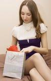 Mädchen schaut ein Geschenk lizenzfreie stockbilder