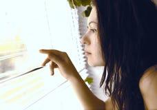 Mädchen schaut heraus das Fenster Stockfotos