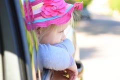 Mädchen schaut heraus das Fenster eines Autos beim Reiten Stockbild