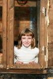 Mädchen schaut heraus von einem hölzernen Fensterfeld Stockfoto