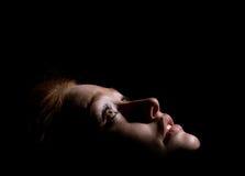 Mädchen schaut oben in der Dunkelheit lizenzfreies stockfoto