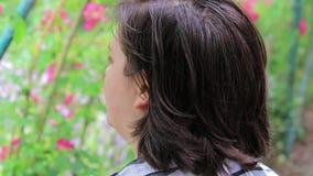 Mädchen schaut vorbei im Garten und lächelt stock footage