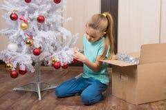 Mädchen schießt Bälle mit Weihnachtsbaum Lizenzfreie Stockfotos