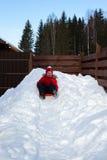Mädchen schiebt unten vom Schneehügel auf Untertasse Lizenzfreie Stockfotos