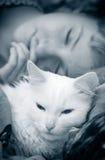Mädchen schläft mit Katze Lizenzfreie Stockfotografie