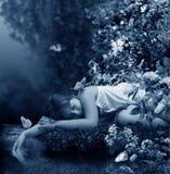 Mädchen schläft neben Nebenfluss Stockbilder