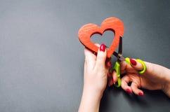 Mädchen schneidet das rote Herz mit Scheren Das Konzept des Brechens von Beziehungen, von Streiten und von Scheidung Verrat des o lizenzfreies stockbild