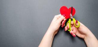 Mädchen schneidet das rote Herz mit Scheren Das Konzept des Brechens von Beziehungen, von Streiten und von Scheidung Verrat des o lizenzfreie stockfotografie