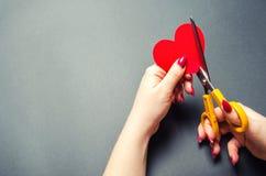 Mädchen schneidet das rote Herz mit Scheren Das Konzept des Brechens von Beziehungen, von Streiten und von Scheidung Verrat des o stockfotos