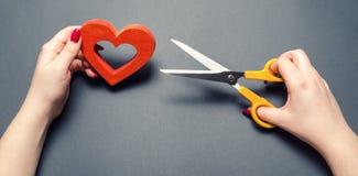 Mädchen schneidet das rote Herz mit Scheren Das Konzept des Brechens von Beziehungen, von Streiten und von Scheidung Verrat des o stockbild