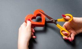 Mädchen schneidet das rote Herz mit Scheren Das Konzept des Brechens von Beziehungen, von Streiten und von Scheidung Verrat des o stockfotografie
