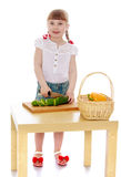 Mädchen schneidet eine Gurke Lizenzfreie Stockfotos